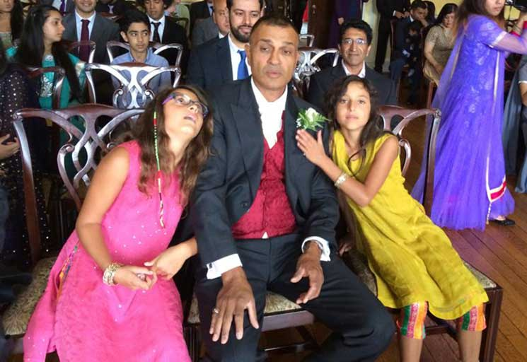 Mo with his twin daughters Kizzy and Leelou at his brother's wedding in 2014
